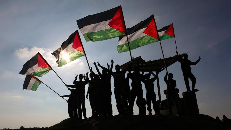 Palestinian protesters wave their national flag near the Israel-Gaza border east of the southern Gaza Strip city of Khan Yunis demonstrating against calls for the closure of UNRWA by the Israeli prime minister and cuts in Palestinian aid by the American president on January 9, 2018. (Said Khartib / AFP)