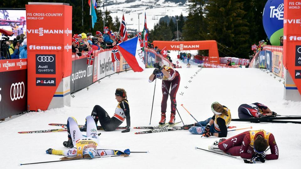 Skiers react in the finish area, after crossing the finish line for the Women's 9 km Pursuit Free - Final Climb race during the FIS World cup Tour de Ski at Val Di Fiemme Cermis's Alps in Cavalese, Italy on January 7, 2018. (Andreas Solaro / AFP)