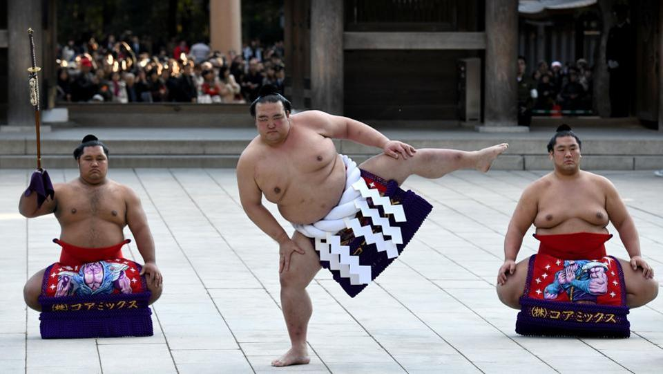 Sumo grand champion Kisenosato (C), performs a ring-entering ceremony beside sword carrier Shohozan (L) and dew sweeper Kagayaki (R) at Meiji shrine in Tokyo on January 9, 2018. Sumo's three grand champions clapped their hands and stamped their feet in a traditional New Year offering to the Shinto gods, as the sport seeks to turn the page on a scandal-hit 2017. (Toshifumi Kitamura / AFP)