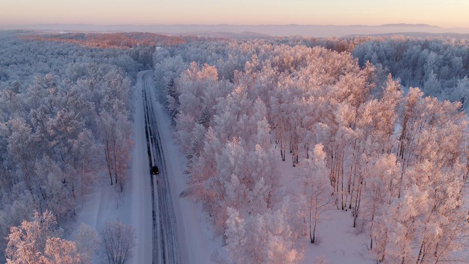 An aerial view shows a car driving along a forest road during sunset, with the air temperature at about minus 27 degrees Celsius in the Siberian Taiga outside the village of Balakhta, Russia on January 5, 2018. (Ilya Naymushin / REUTERS)