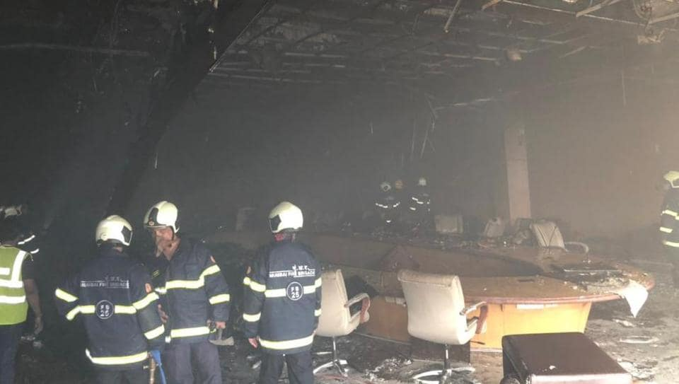 Fire brigade personnel douse fire that broke out on the ground floor conference hall of the Mumbai airport.