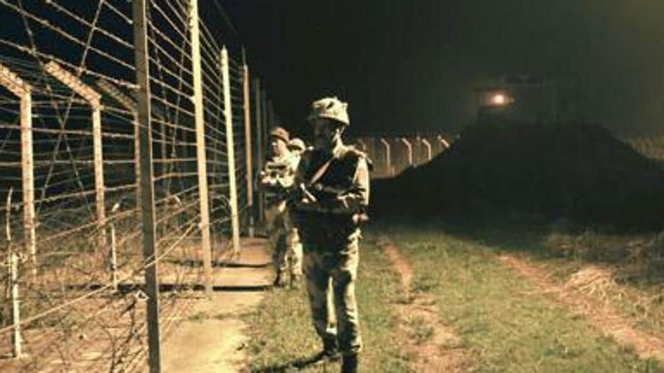 BSF soldiers standing guard during a night patrol near the fence at the India-Pakistan International Border at the outpost of Akhnoor sector.