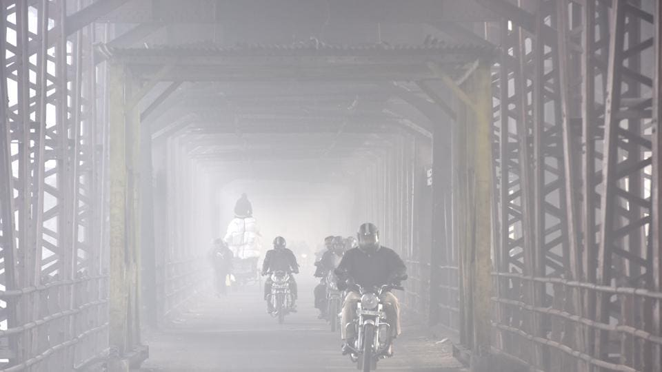 File photo of commuters riding through thick of fog in New Delhi.