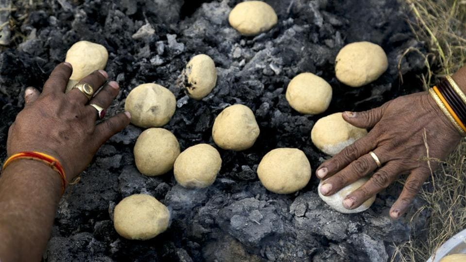 People make Litti for their evening meal before leaving the transit camp to Gangasagar, in Kolkata. Thousands of Hindu pilgrims are expected to take the annual holy dip at Gangasagar, where the Ganges River reaches the Bay of Bengal, on the auspicious Makar Sankranti festival day that falls on January 14. (Bikas Das / AP)
