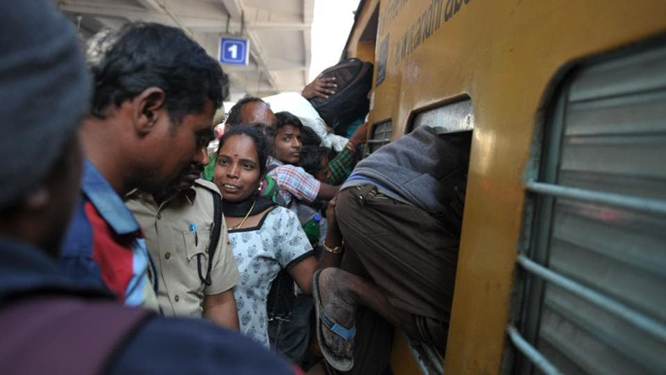 A passenger climbs into a train bound for coastal districts in the state of Andhra Pradesh at Secunderabad Railway Station in Hyderabad. (Noah SEELAM / AFP)