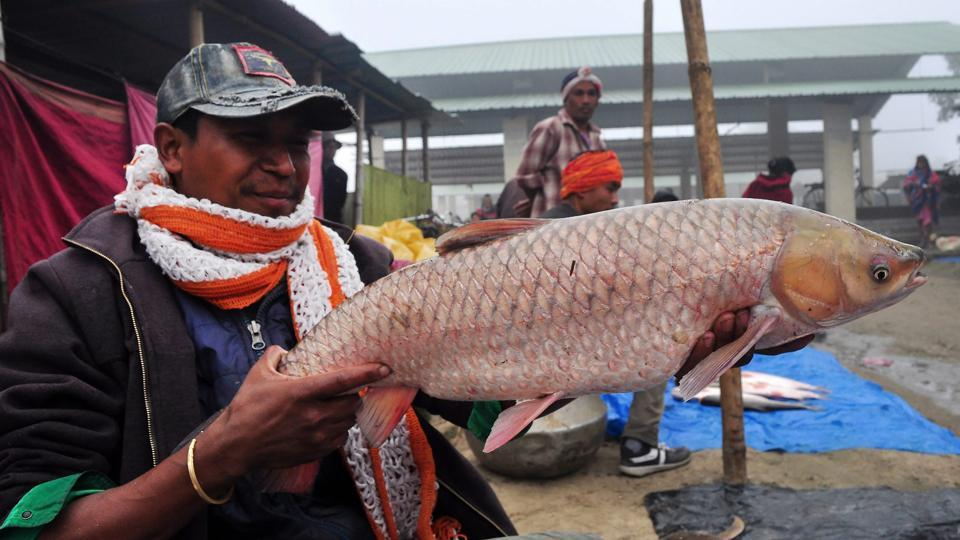 A man sells fish at a market on the occasion of harvest festival Magh Bihu in Assam. (PTI)