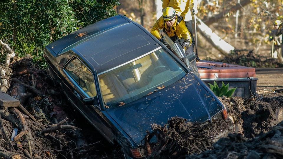 Rescue workers search a car after a mudslide in Montecito.