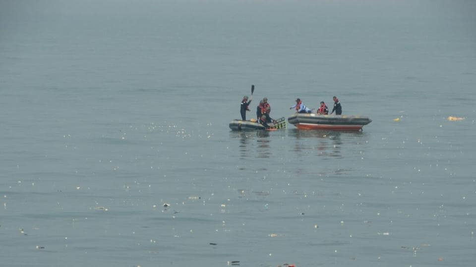 Indian Coast Guard personnel search for missing people off the coast of Mumbai after a helicopter crash on Saturday.
