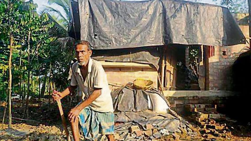 Alamgir Mondal's grandfather Maijuddin Mondal in front of their unfinished home.
