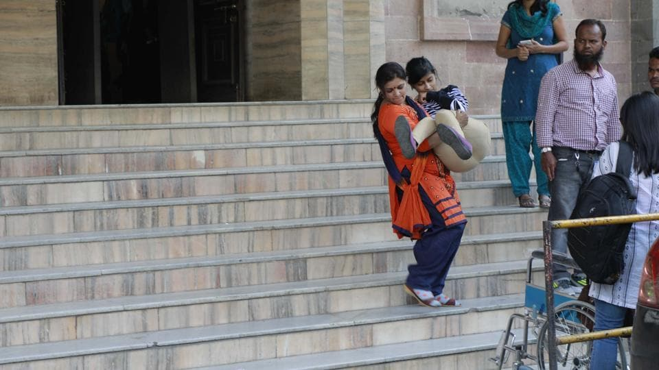 Twenty-four-year-old Diksha Dinde being carried down the staircase of the Pune Municipal Corporation (PMC) main building by her mother in the absence of a ramp.