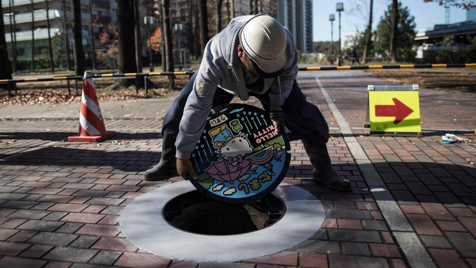 "A worker installs a new manhole lid bearing Hello Kitty at Tama Chuo Park. And manhole covers don't simply hide dirty sewers; there is a story even to plain covers -- such as finding the logos of defunct companies, enthuses Tetsuro Sasabe, a manholer. ""I'm interested in why the manhole is there, where it leads to -- I'd say I'm interested in what's under the manhole covers,"" he said. (Behrouz Mehri / AFP)"