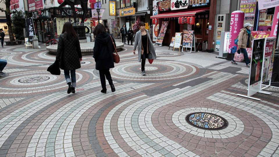People walk past designed manhole covers in Kawaguchi. The craze has since spread online with abundant information on where to find the best manholes via the hashtag #manhotalk. (Behrouz Mehri / AFP)