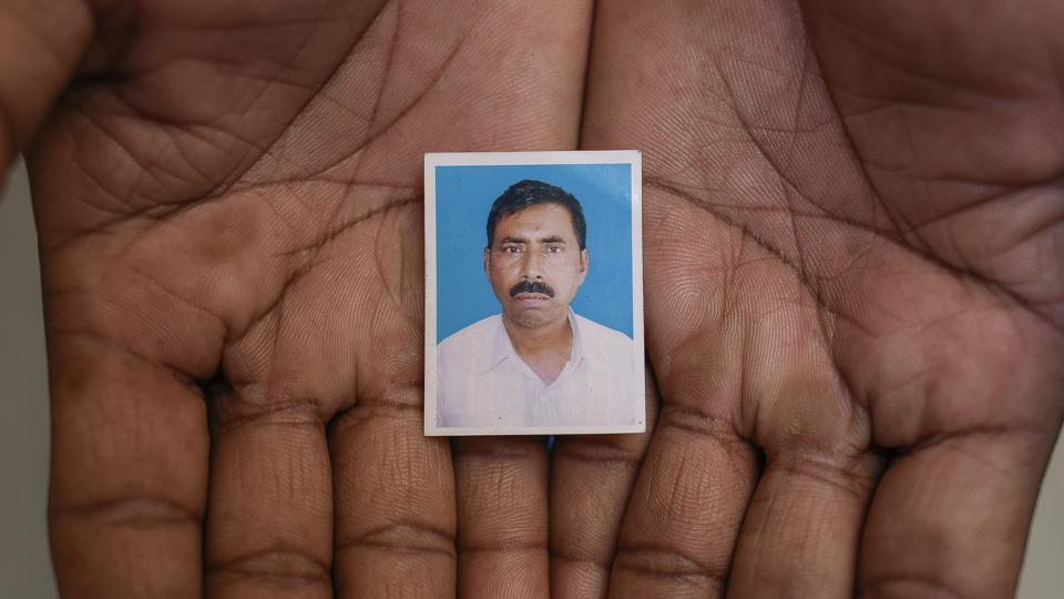 A passport photograph of Afrajul as held by his brother Rumkhan  in Saiydpur in Malda. (Burhaan Kinu / HT Photo)