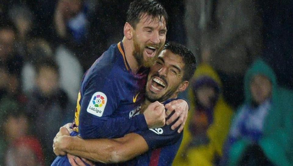 Barcelona's Lionel Messi celebrates with Luis Suarez after scoring their fourth goal in La Liga against Real Sociedad at the Anoeta Stadium in San Sebastian onSunday.