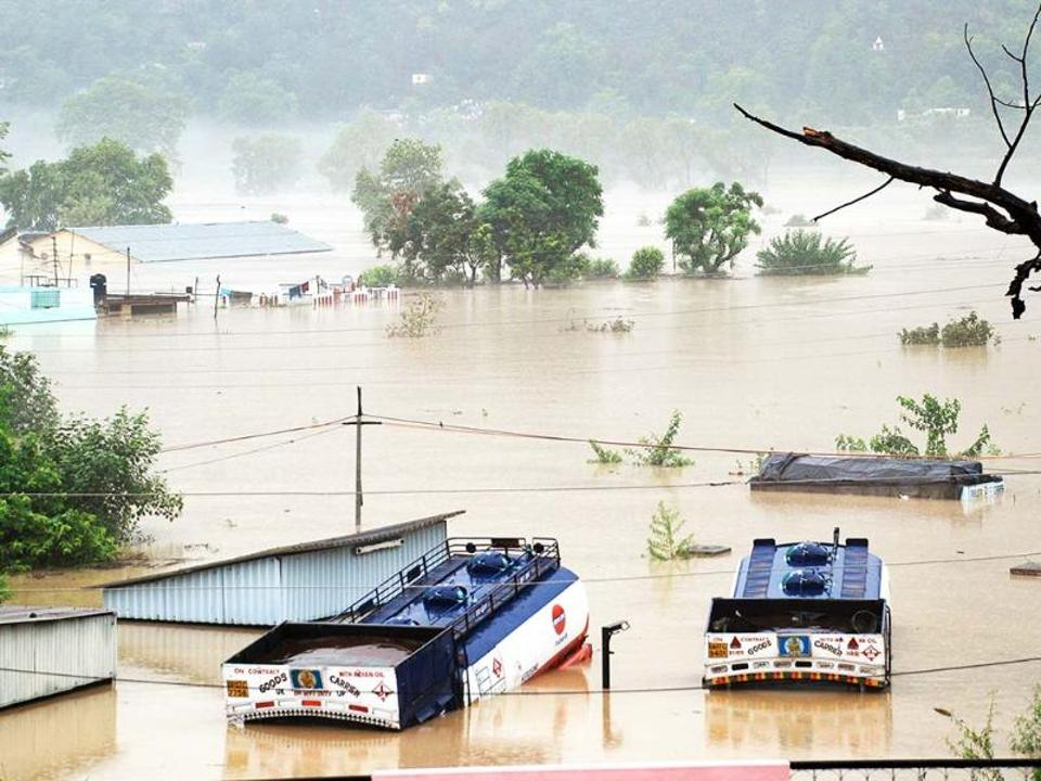 Houses are submerged as trucks flow in flood waters of the Bhagirathi River in Shrinagar district Uttarakhand. AP