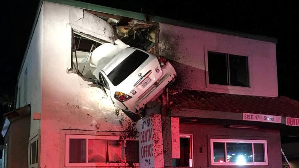 A car dangles off the second floor of a building after speeding into a median and going airborne, according to authorities in Santa Ana, California.