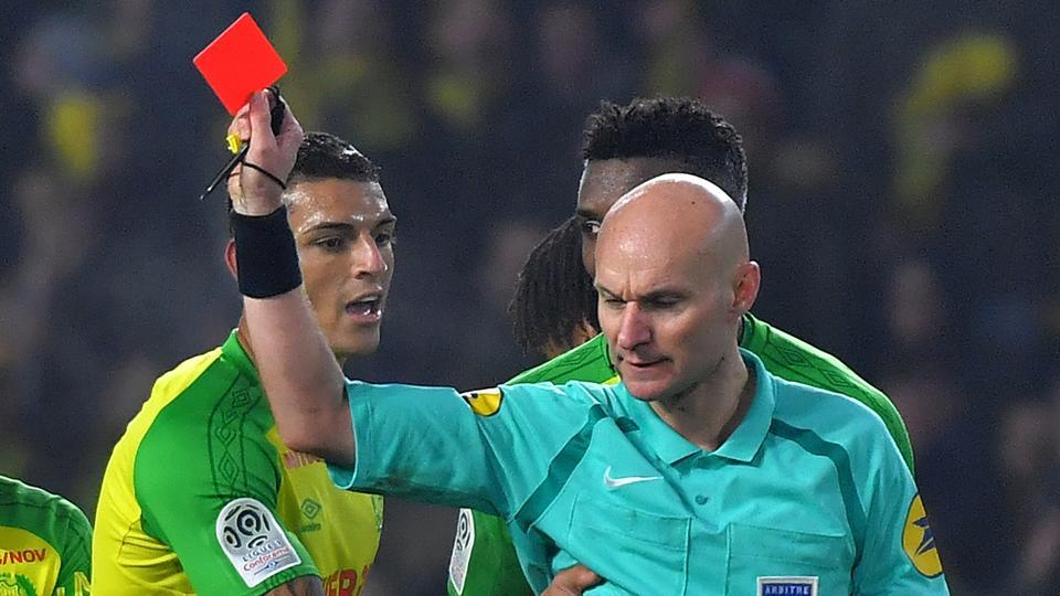 Nantes' defender Diego Carlos (L) receives a red card from French referee Tony Chapron during the Ligue 1 match vs Paris Saint-Germain at the La Beaujoire stadium in Nantes on January 14, 2018. Chapron was provisionally suspended for appearing to kick at Carlos before sending him off.