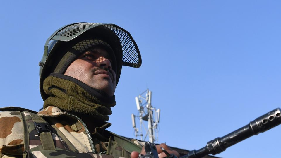 A paramilitary trooper stands guard in Srinagar on January 15. The Indian Army said it had killed Pakistani soldiers in fighting in along the Line of Control in Jammu and Kashmir .