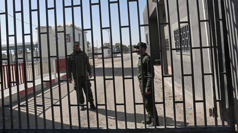Palestinian security forces loyal to the Palestinian Authority (L) stand at the gate of the Kerem Shalon crossing, the main passage point for goods entering Gaza, after is was closed by Israel following the discovery of smuggling tunnels underneath the crossing, in the southern Gaza Strip town of Rafat on January 14, 2018.