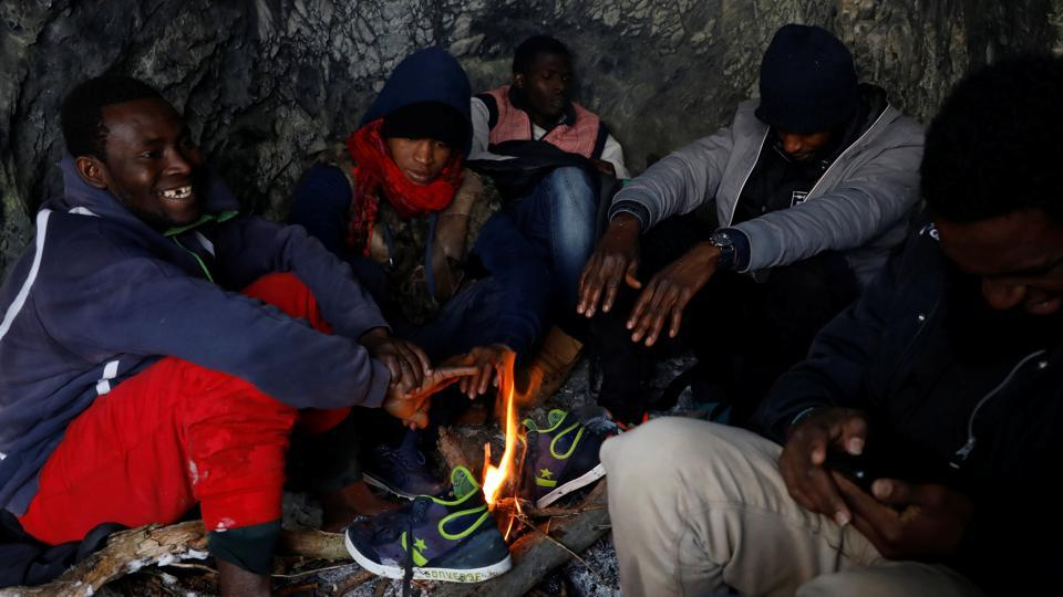 "Kamarra, 28 (L), from Guinea and other migrants warm up by a fire in a cave after crossing part of the Alps. ""I was imprisoned and tortured in Libya for many months. I was forced to work for free. Just look at my scars,"" he said, lifting his clothes to show marks on his body. (Siegfried Modola / Reuters)"