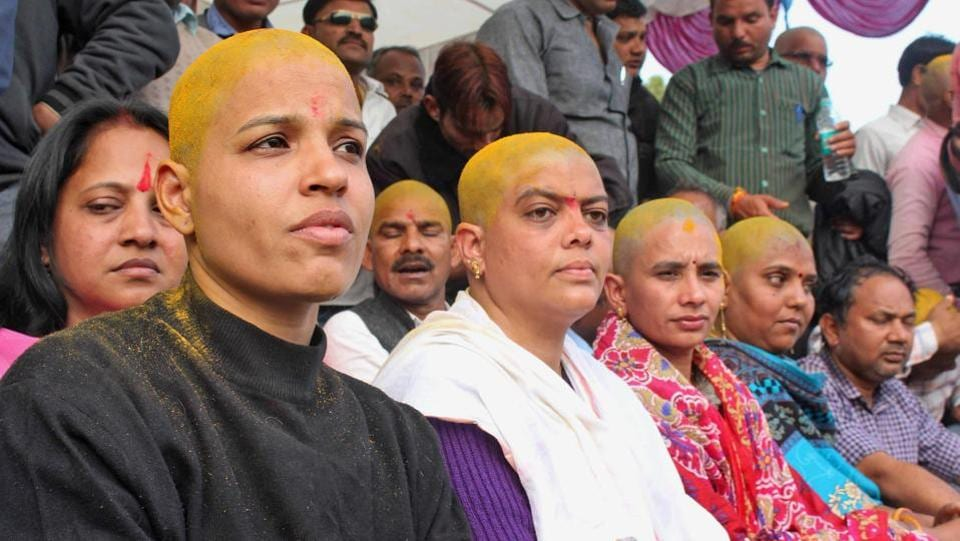 Female teachers, with their heads tonsured, take part in an 'Adhikar Rally' demanding the merger of their services with that of teachers on the roll in the state and payment as per the 7th pay commission, in Bhopal on Saturday. The protest today spread to other places in Madhya Pradesh such as Gwalior and Sagar. (PTI)