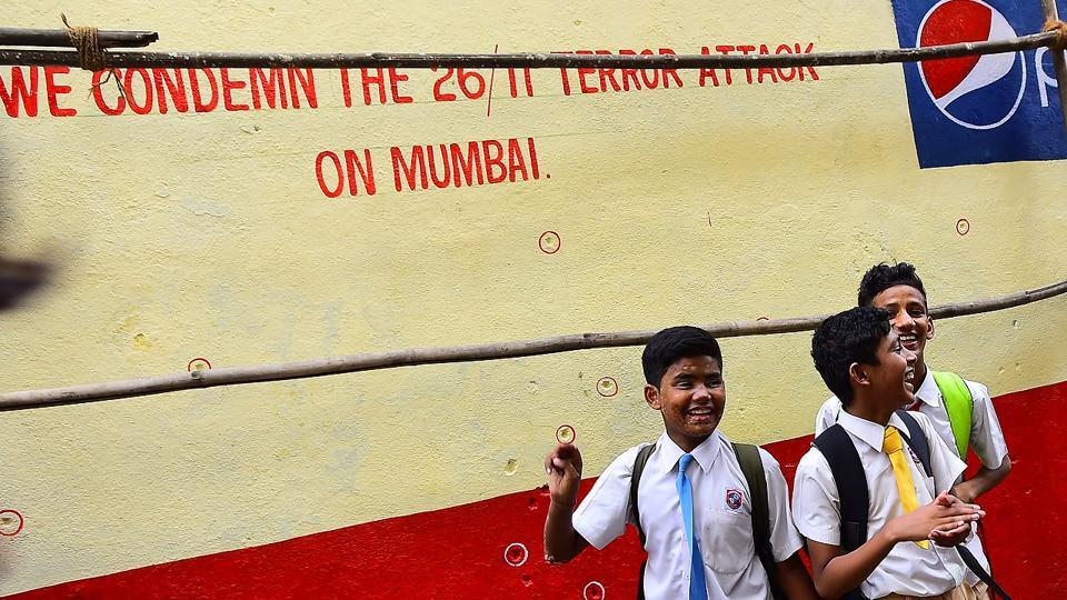 Schoolchildren walk past a wall pock-marked with bullet holes opposite the Nariman House. (Vijayanand Gupta/HT Photo)