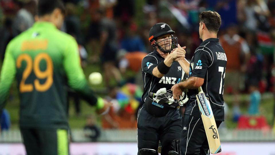 New Zealand cricket team's Henry Nicholls (C) and Colin de Grandhomme (R) celebrate after beating Pakistan cricket team in the fourth one-day international at Seddon Park in Hamilton on Tuesday.