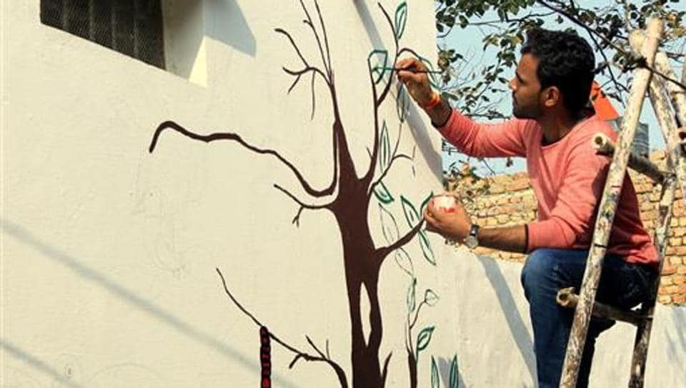 A volunteer paints walls in Kherla village of Nuh tehsil in Mewat district.