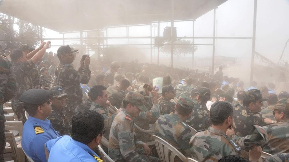 Dust surrounds around the spectators during a Army fire drill at KK Range, Ahmednagar. (HT PHOTO)