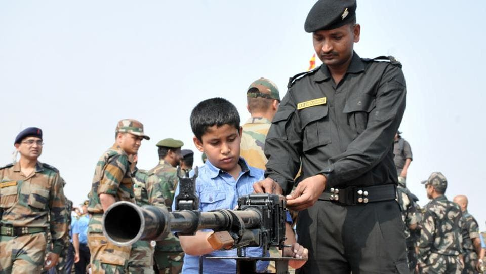 A child looks at a  weapon during the Army fire drill at KK Range, Ahmednagar in Pune. (HT PHOTO)