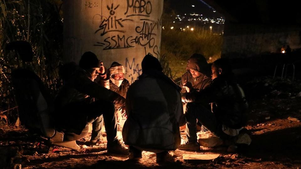 Migrants mostly from the Darfur region of western Sudan warm up by a fire under a highway bypass in Ventimiglia where they have been sheltering in preparation to attempt the crossing into France. (Siegfried Modola / Reuters)