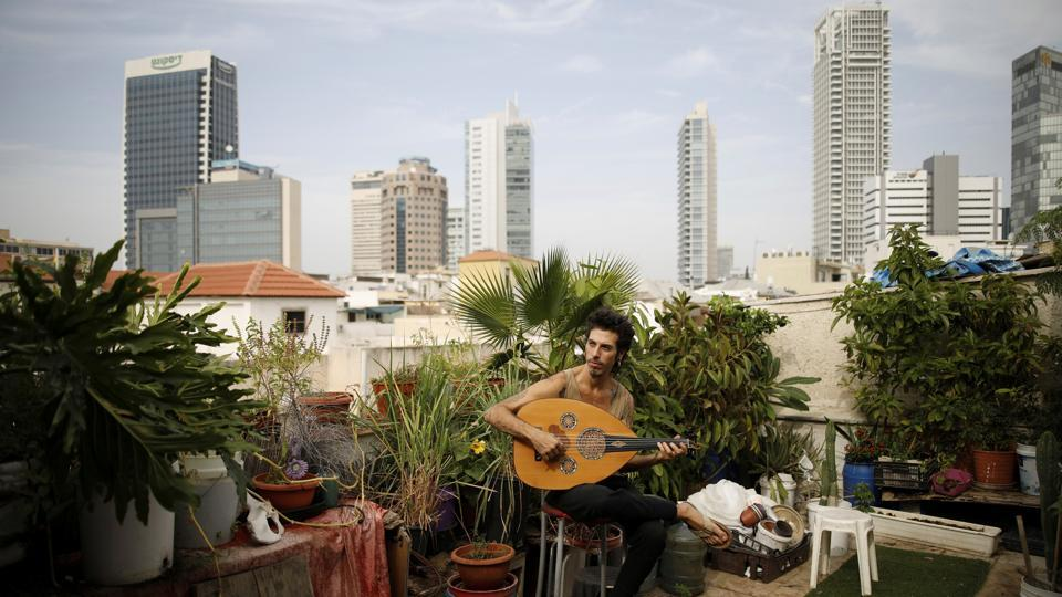 Musician Iyar Semel, 38, plays an oud on his rooftop garden, where he grows herbs and vegetables with his flatmates in Tel Aviv, Israel. Iyar planted an organic garden on his rooftop, with compost, vegetables, fruit trees and a shower. It all allows him to merge his ecological lifestyle with the restraints of urban space. (Corinna Kern / REUTERS)