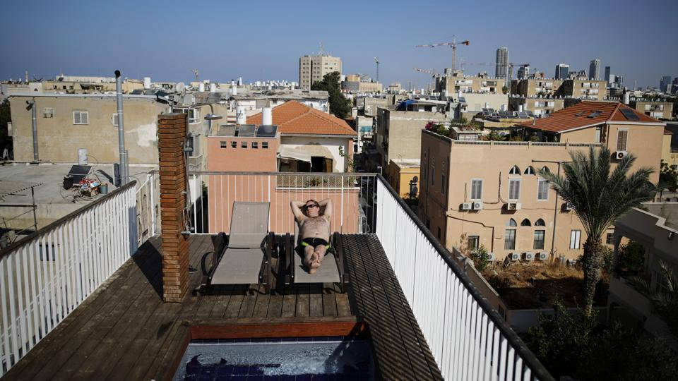 Aviah Morag, 25, sunbathes on his rooftop, equipped with a small pool, a shower and deck chairs. When it comes to cutting back from the urban hustle, Tel Aviv's residents need look no further than their own rooftops. (Corinna Kern / REUTERS)