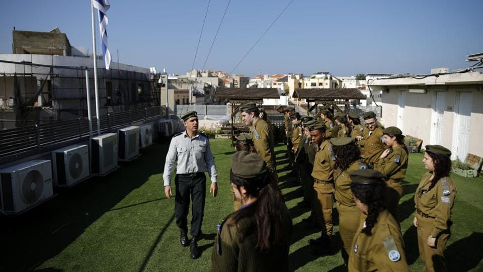 Israeli soldiers prepare for a parade in front of the master-sergeant who is checking their appearance, on the rooftop of the Israeli Defence Forces Galgalatz radio station, in Tel Aviv. This routine takes place twice a week and occurs frequently on the station's rooftop. (Corinna Kern / REUTERS)