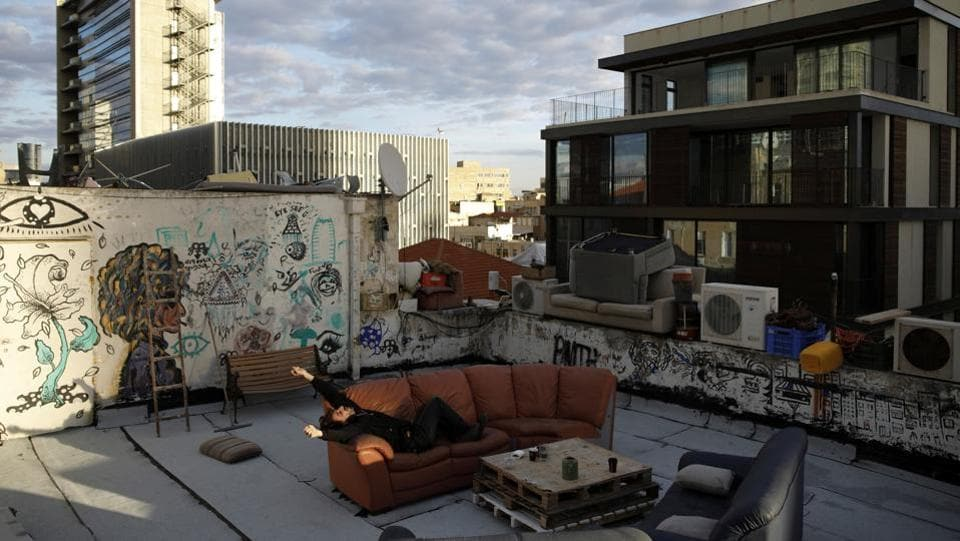 Guy Elhadad, 26, lies on a sofa on his rooftop in Tel Aviv. For Guy his rooftop is his creative incubator,