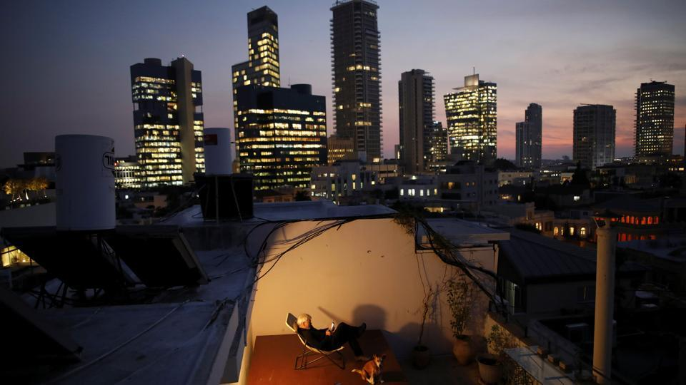 Alexander Flaschenberg, 60, sits on a chair placed on top of a table, in order to enjoy view of the sea from his rooftop in Tel Aviv. The rooftop is a personal haven for Alexander, giving him an opportunity to unwind from work. (Corinna Kern / REUTERS)
