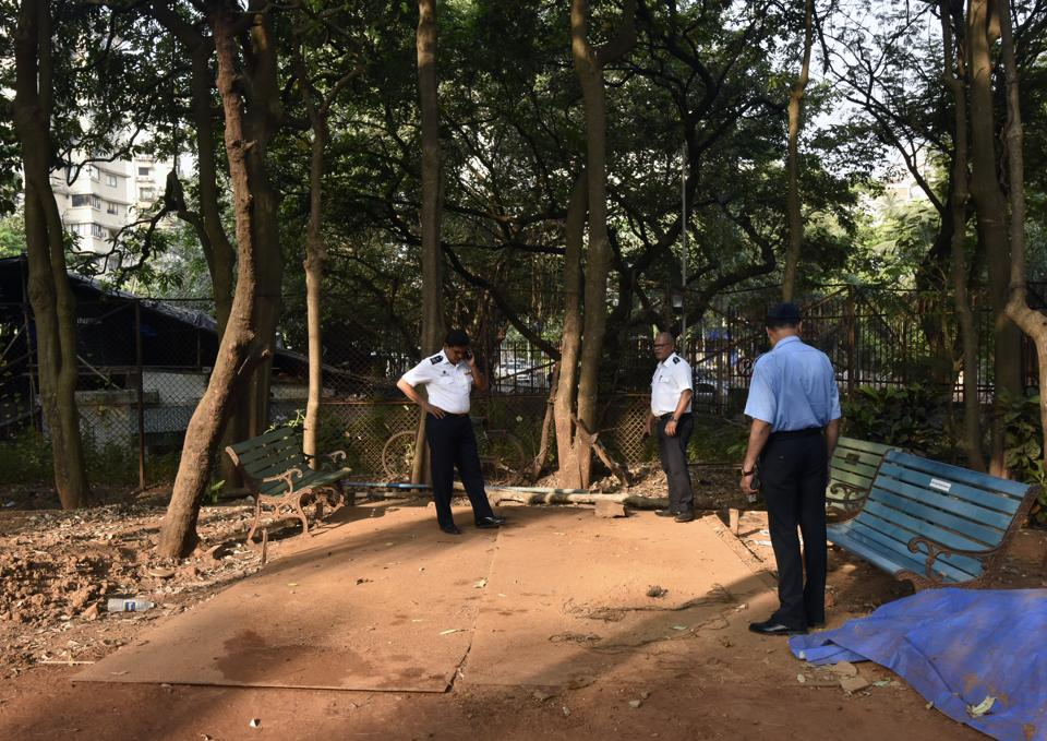 Fire officials inspect the area after removal of the fire truck and demolition of the shed at Priyadarshini park