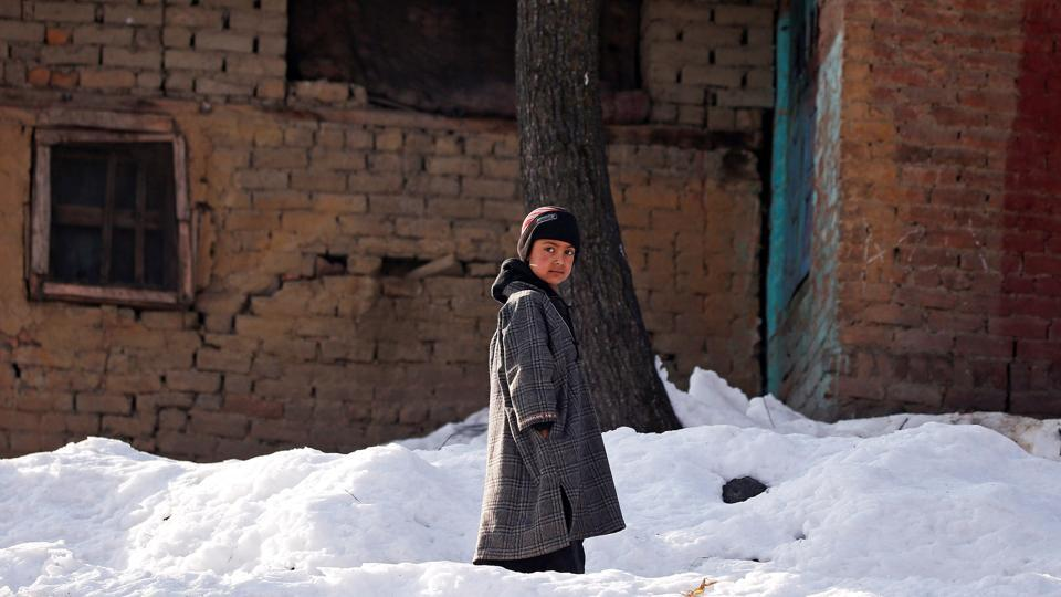 A boy stands on snow outside his home on a cold winter morning at Haripora Village, South Kashmir.