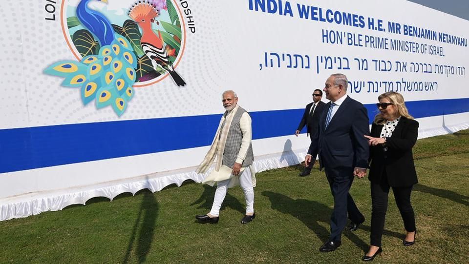 Narendra Modi (L), Israeli Prime Minister Benjamin Netanyahu (C) and his wife Sara Natanyahu walk past a billboard during an official visit to Ahmedabad. Modi and Netanyahu inaugurated the iCreate Centre at Deo Dholera village later in the afternoon. They will also visit a Startup Exhibition and interact with innovators and Startup CEOs. (AFP / PIB)
