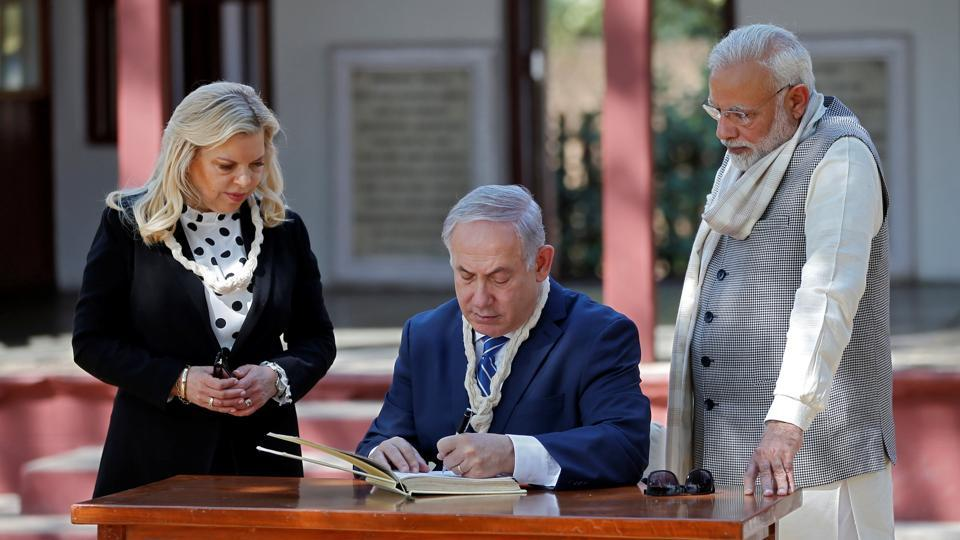 Israeli Prime Minister Benjamin Netanyahu writes a message in the visitor's book at Gandhi Ashram as his wife Sara and his Indian counterpart Narendra Modi look on. Netanyahu and his wife Sara also garlanded a photo of Mahatma Gandhi. (Amit Dave / REUTERS)