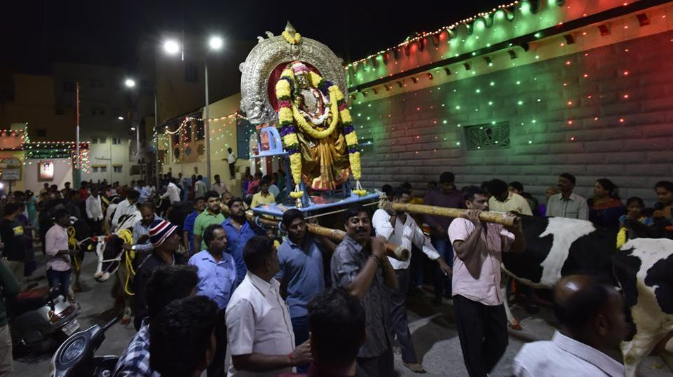An idol of the goddess Patalamma, an incarnation of Durga, is carried during Sankranti celebrations in Bengaluru. Nearly forty heads of cattle also marched in the procession after being worshipped at a temple before sunset.  (Arijit Sen / HT Photo)