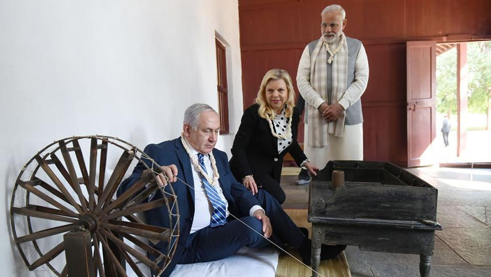 Israeli Prime Minister Benjamin Netanyahu (L) tries his hand at the spinning wheel as PM Narendra Modi and Sara Netanyahu look on during a visit to the Sabarmati Ashram in Ahmedabad. The Israeli Prime Minister and his wife landed in Ahmedabad to a packed schedule, hosted by PM Modi himself.  (AFP / PIB)
