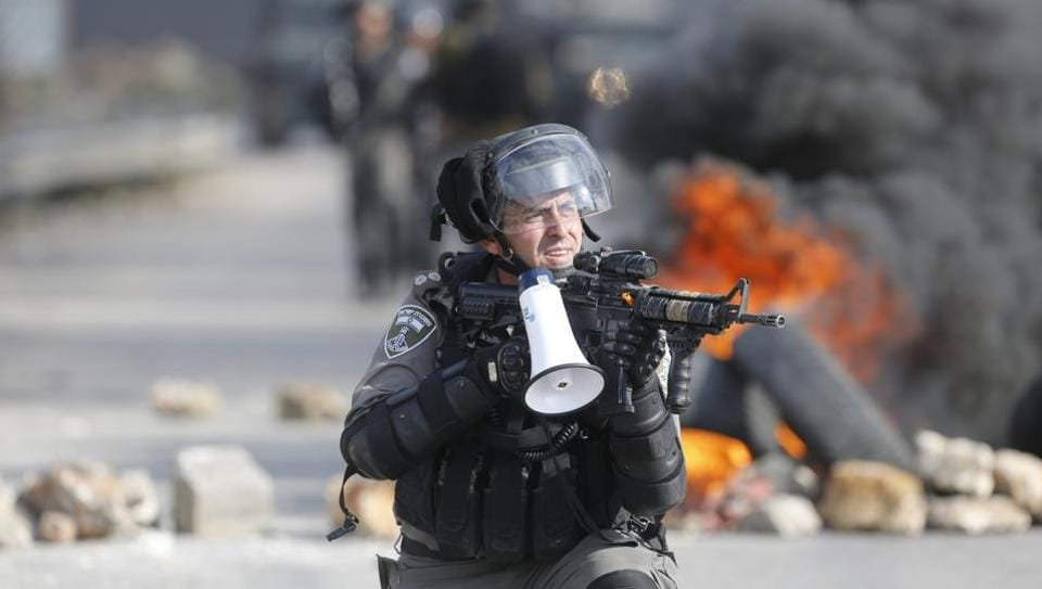 An Israeli border guard takes position during clashes following protests against US President Donald Trump's decision to recognize Jerusalem as the capital of Israel, in the West Bank city of Ramallah, Friday, Jan. 12, 2018.
