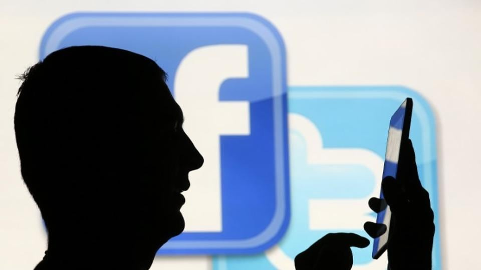 A man is silhouetted as he uses a mini tablet computer while standing in front of a video screen with the Facebook and Twitter logos