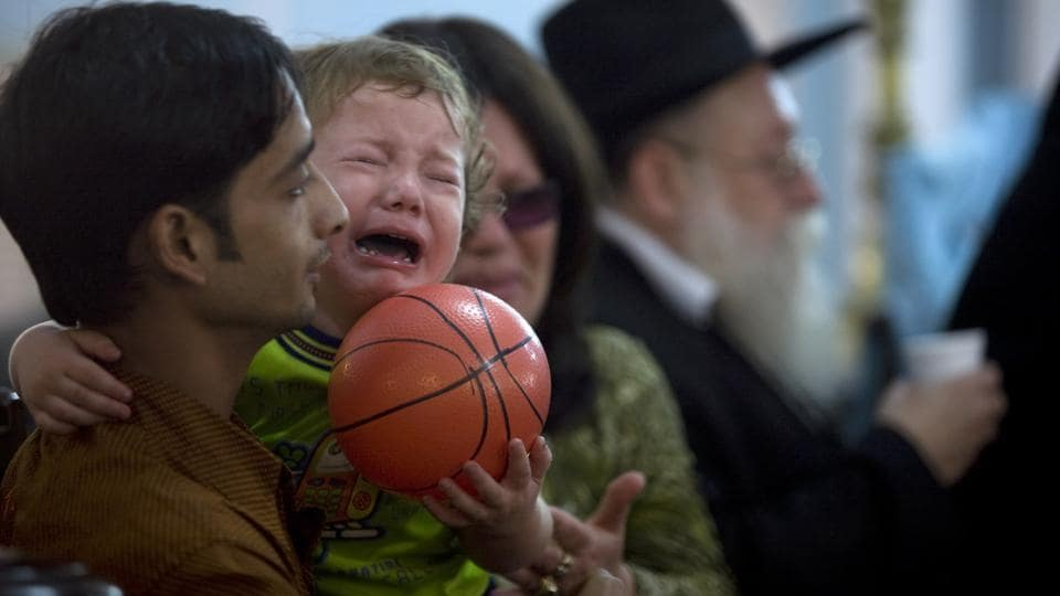 Two-year-old Moshe Holtzberg is held by his grandmother Yehudit Rosenberg as grandfather Shimon Rosenberg looks on during a condolence prayer meeting in a synagogue, for those killed by armed militants at the Jewish centre. The young boy, who was just two days short of turning two when the attack took place,unveiled a memorial dedicated to the victims  of the 26/11 attacks, along with Israeli Prime Minister Benjamin Netanyahu. (HT File Photo)