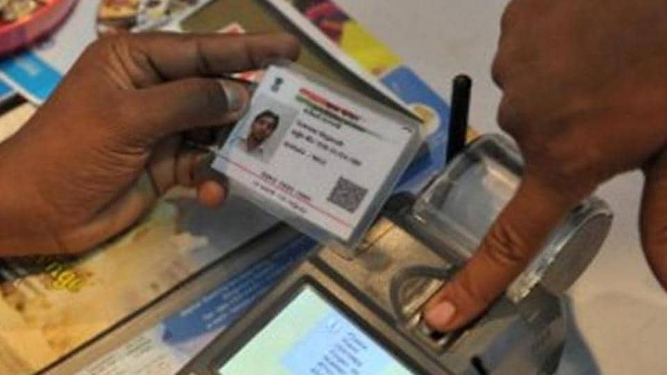 A visitor gives a thumb impression to withdraw money from his bank account with his Aadhaar or Unique Identification (UID) card in Hyderabad on January 18, 2017.