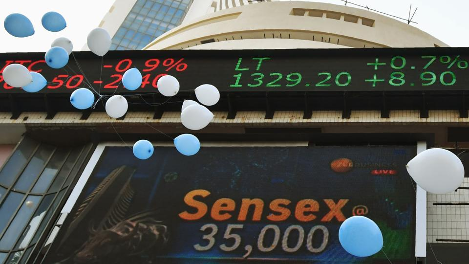 Indian workers release balloons outside the Bombay Stock Exchange (BSE) to celebrate the benchmark 30-share index SENSEX crossing 35,000 points in Mumbai on January 17, 2018. / AFP PHOTO / PUNIT PARANJPE