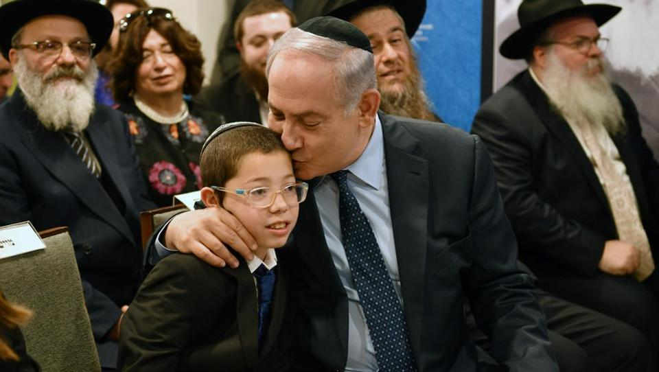 Israel Prime Minister Benjamin Netanyahu (R) sits with Moshe Holtzberg, during a memorial for the 26/11 victims at Nariman House in Mumbai on January 18, 2018. Moshe, who survived the siege at Nariman House arrived on Tuesday morning for the first time since his parents' death. (Indranil Mukherjee / AFP)
