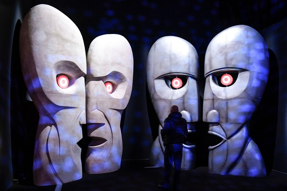 A visitor looks at a replica of the 'The Division Bell Metal Heads' at the Pink Floyd Exhibition. The exhibits comprise installations, instruments and album art work, taking visitors through the band's origins in the 60s to present day. (Andreas Solaro / AFP)