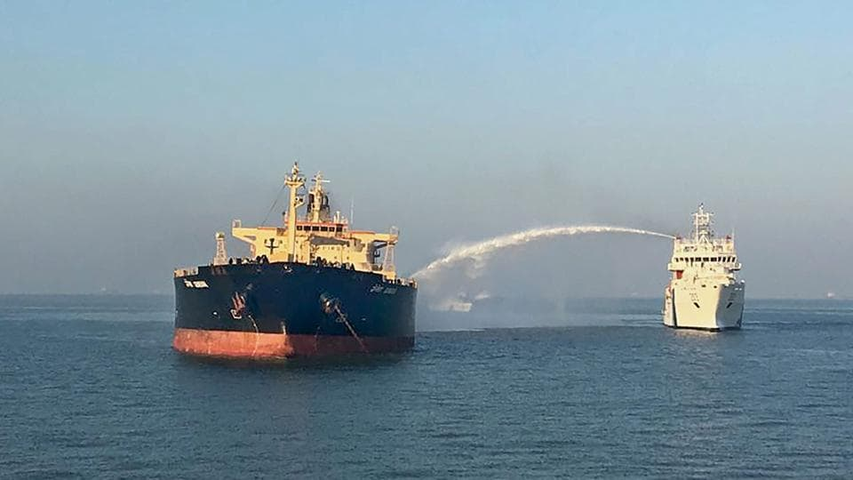 A ship douses the flame and cools off the temperature of M T Genessa in Kandla on Thursday.